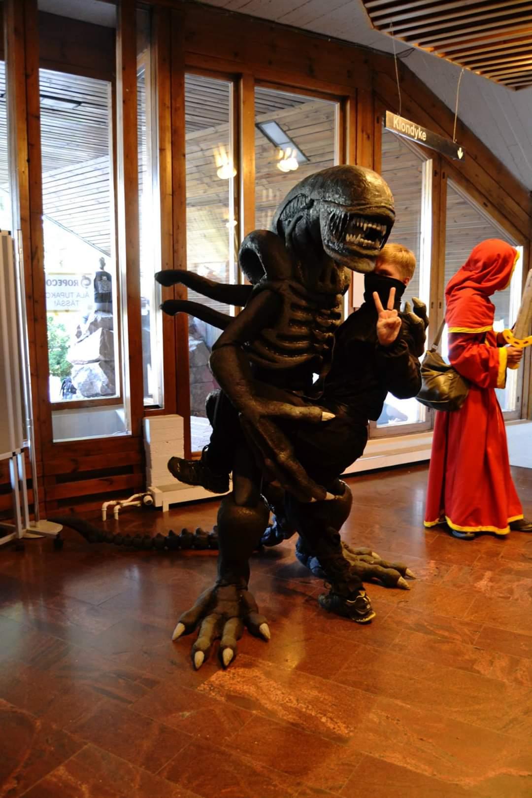 Alien hahmoksi pukeutunut hennkilö pitelee sylissään ninjaksi pukeutunutta henkilöä.