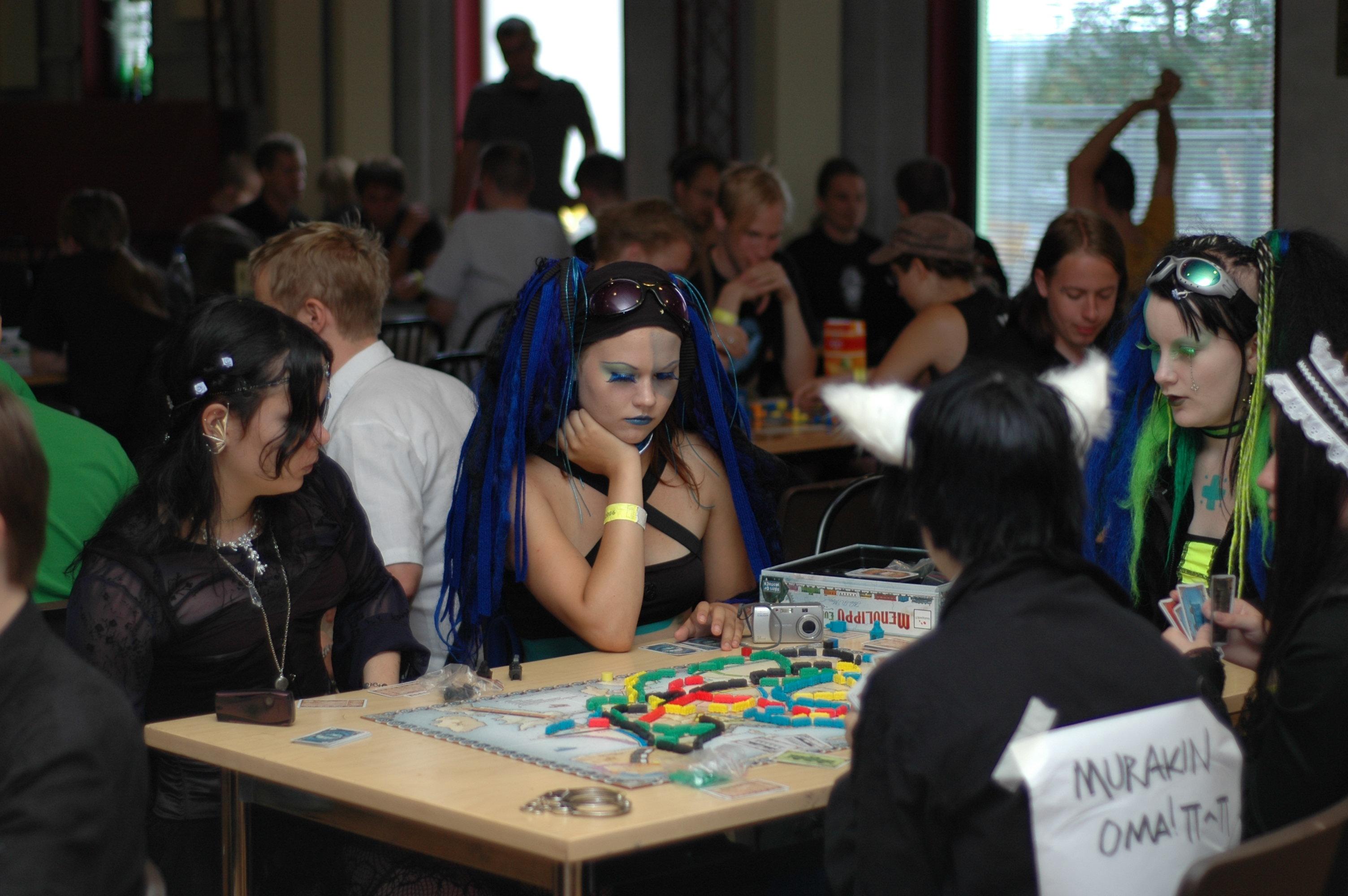 Neljä ihmistä pelaamassa lautapeliä.