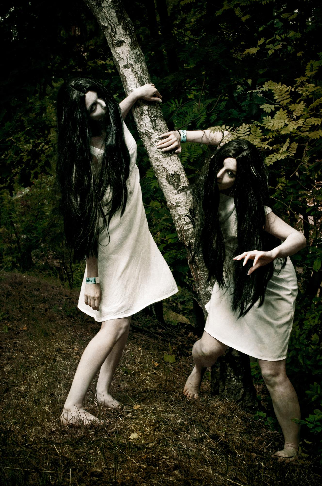 Kaksi aavemaista neitoa puun edessä.