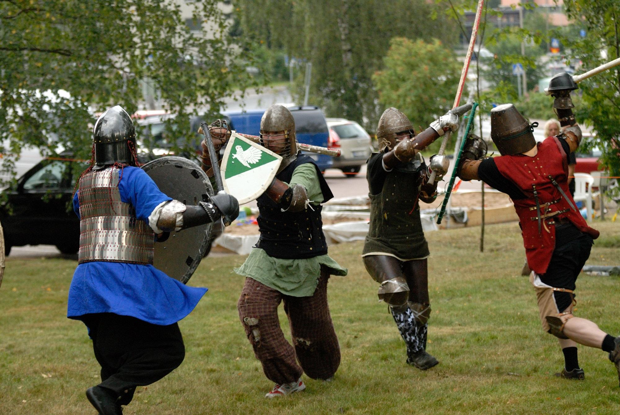 Ritariasuisia henkilöitä taistelemassa bofferimiekoilla..